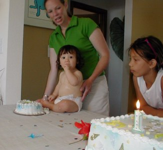 Landon eating his own personal cake with mom, Gina and his cousin,Tiarra Paige watching
